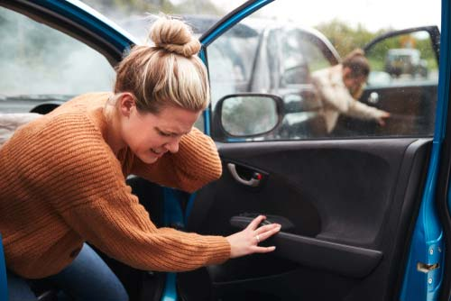 A woman getting out of her car after an accident.